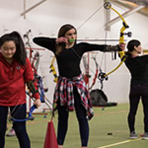 This image shows a girl at an archery program