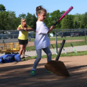 This image shows a kid swinging a bat at tball.
