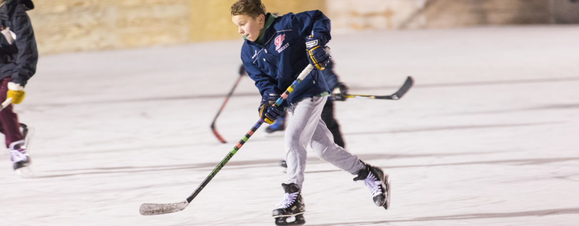This image shows an image of a kid playing ice hockey.