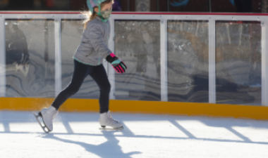 This image shows a young girl skating on the rink at Broadway Square.