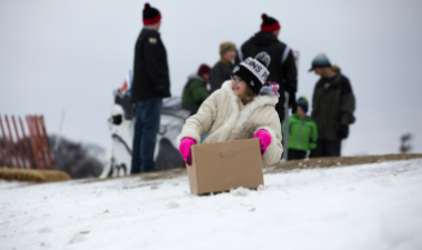 This image shows a child sledding in a cardboard box.