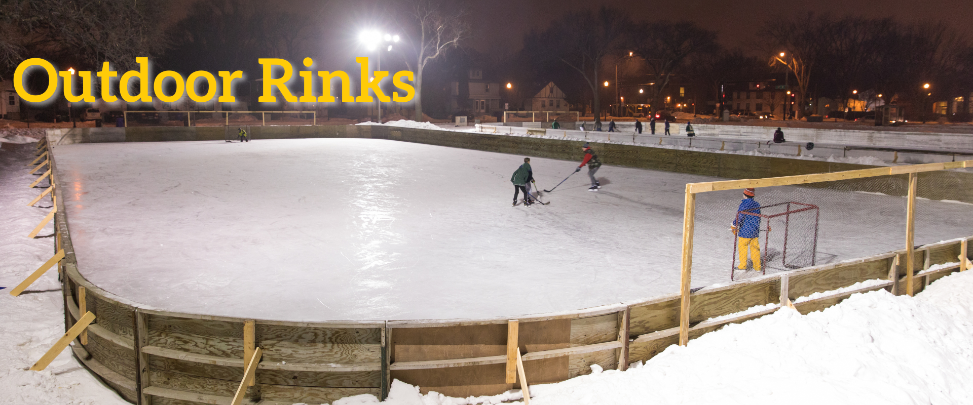 This image shows four people playing hockey on an outdoor ice rink.