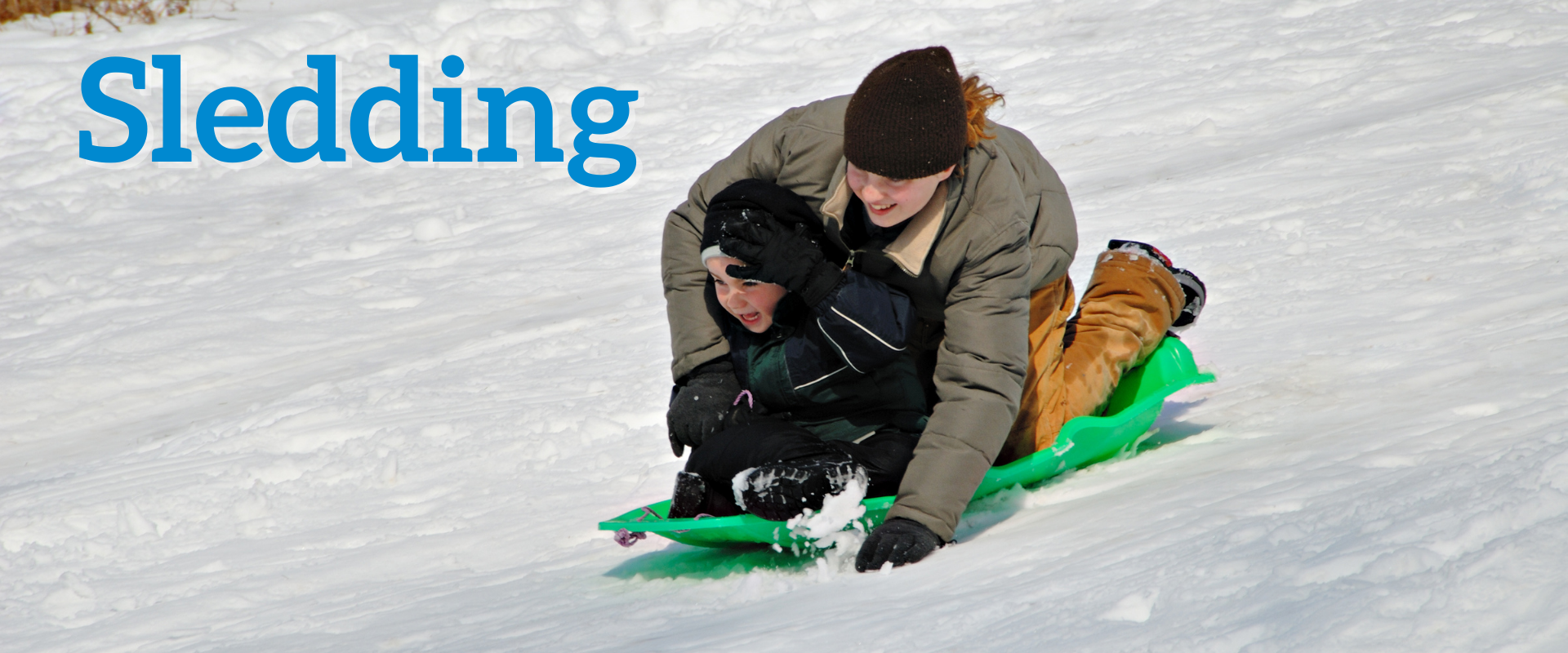 This image shows two kids on a sled sledding down the hill.