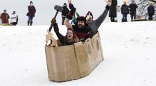 This image shows three people going down in a cardboard sled at the 2017 race