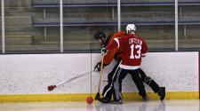 This image shows two players along the boards during broomball.