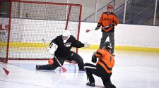 This image shows the goalie stopping a shot during adult broomball.
