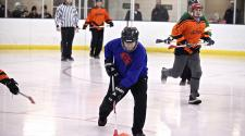 This image shows one guy trying to get the ball up the ice and teammates following during adult broomball.