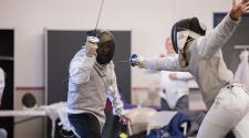 This image shows two children in a fencing duel at the youth fencing program.