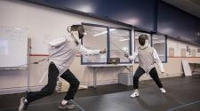 This image shows two children learning how to fence at the youth fencing program.
