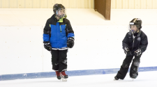 This image shows two boys skating at Open Hockey.