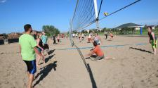 This image shows a sand volleyball match being played.