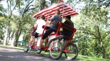 This image shows a group of four people riding a single surrey bike at Lindenwood Park.