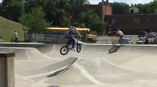 This image shows two people on BMX bikes at the skate park.