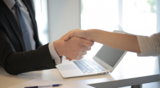 This image shows two business people shaking hands over a desk and computer.
