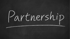 This image shows the word partnership written on a black board.