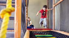This image shows kids playing on the indoor playground at Courts Plus.