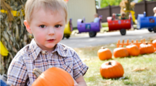 This image shows a boy holding a pumpkin at Fall in Fargo.