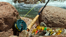 This image shows a fly fishing rod and supplies on some rocks next to the water.
