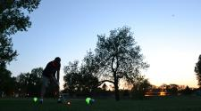 This image shows a male getting ready to tee off at Glow Golf.