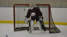 This image shows a goalie getting ready to make a save at youth hockey skills training.