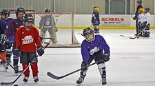 This image shows a group of players getting ready to start a drill at youth hockey skills training.