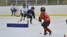 This image shows two kids doing a drill at youth hockey skills training.