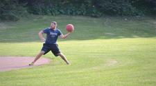 This image shows a male throwing the kickball during kickball league.