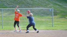 This image shows a female trying to get another player out at a base during kickball league.
