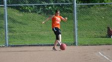 This image shows a female kicking the ball during kickball league.
