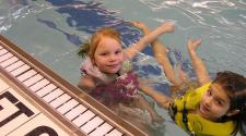 This image shows two girls in the pool at Open Swim.