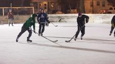 This image shows a game of hockey happening on an outdoor rink.