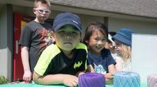 This image shows two kids smiling for the camera during a yarn project at Park It.
