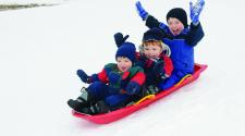 This image shows three boys on one sled sledding down the hill together.