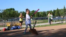 This image shows a girl hitting the ball at the youth tee-ball program.
