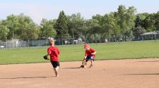 This image shows a boy fielding the ball during the youth tee-ball program.