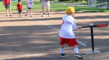 This image shows a boy hitting the ball at the youth tee-ball program.