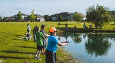 This image shows some kids casting their rods into the pond at Trout Fest.
