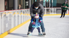 This image shows a father teaching his young child how to skate on the skating rink at Broadway Square.